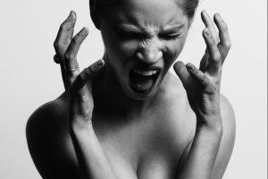 Een vrouw in zwartwit die schreeuwt van de frustratie van haar prikkelbare darm syndroom die op te lossen is met hypnose behandeling tegen spastische darm