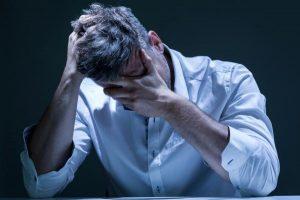Een man in een wit overhemd die gek wordt van zijn tinnitus klachten die zijn te behandelen met hypnose tinnitus behandeling