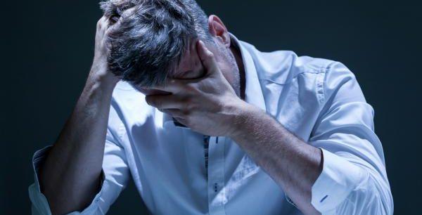 Een man in een wit overhemd die gek wordt van zijn chronische medische pijn die zijn te behandelen met hypnose